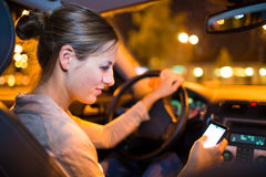 Giovane donna graziosa che per mezzo del suo Smart Phone mentre conducendo la sua automobile Immagini Stock