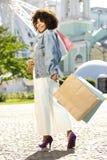 Giovane donna graziosa che porta molti sacchetti della spesa immagini stock libere da diritti
