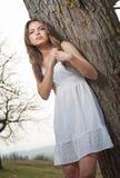 Giovane donna graziosa che posa mettendo su un albero. Ragazza bionda molto attraente con breve all'aperto bianco su una collina.  Immagine Stock
