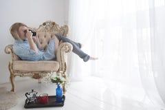 Giovane donna graziosa che prende una foto attraverso la finestra immagine stock libera da diritti