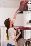 Giovane donna graziosa che raggiunge per una borsa sull'alto scaffale Immagine Stock Libera da Diritti