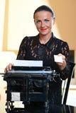 Giovane donna graziosa che si siede ad una macchina da scrivere Fotografia Stock
