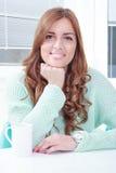 Giovane donna graziosa che si siede con la tazza di caffè fotografia stock libera da diritti