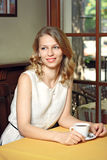 Giovane donna graziosa che si siede nel caffè con una tazza di caffè Immagini Stock Libere da Diritti