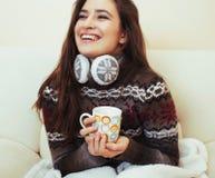 Giovane donna graziosa che si siede nella sedia comoda con caffè e fotografia stock libera da diritti
