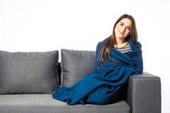 Giovane donna graziosa che si siede sul sofà coperto di coperta su bianco fotografie stock libere da diritti