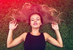 Giovane donna graziosa che si trova nell'erba e nel sogno Immagine Stock Libera da Diritti