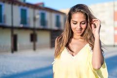 Giovane donna graziosa che sorride vicino su all'aperto con un vestito giallo Immagini Stock
