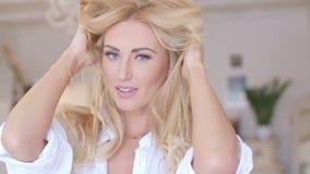 Giovane donna graziosa che tiene i suoi capelli biondi lunghi archivi video