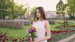 Giovane donna graziosa che tiene un mazzo di bei fiori Mano femminile che tocca i bei fiori Godere della natura stock footage