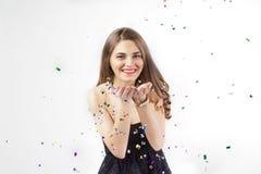 Giovane donna graziosa con i sorrisi dei coriandoli fotografia stock libera da diritti