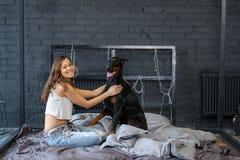 Giovane donna graziosa con il cane nero del doberman Fotografia Stock
