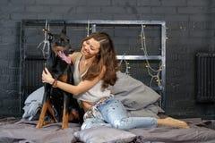 Giovane donna graziosa con il cane nero del doberman Fotografia Stock Libera da Diritti