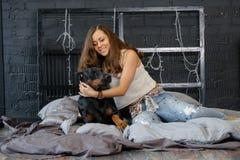 Giovane donna graziosa con il cane nero del doberman Immagini Stock