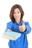 Giovane donna graziosa con il libro che mostra i pollici su Immagine Stock