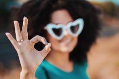 Giovane donna graziosa con l'acconciatura riccia africana e gli occhiali da sole in forma di cuore che mostrano segno GIUSTO Bell fotografie stock