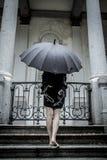 Giovane donna graziosa con l'ombrello nero, sotto la pioggia di autunno in una p Fotografia Stock