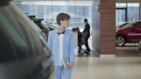 Giovane donna graziosa con la compressa in mani nel vestito blu di usura convenzionale che cammina fra le file di nuove automobil video d archivio