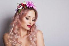 Giovane donna graziosa con la corona dei fiori rosa Fotografia Stock