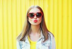 Giovane donna graziosa del ritratto in occhiali da sole rossi che soffiano bacio delle labbra sopra giallo Immagini Stock