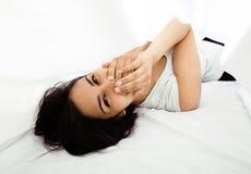Giovane donna graziosa del tann a letto fra divertiresi bianco degli strati, provando a dormire, imbrogliante intorno Fotografia Stock