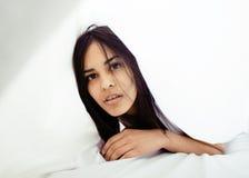 Giovane donna graziosa del tann a letto fra divertiresi bianco degli strati, provando a dormire, imbrogliante intorno Fotografia Stock Libera da Diritti
