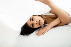 Giovane donna graziosa del tann a letto fra divertiresi bianco degli strati, provando a dormire, imbrogliante intorno Fotografie Stock