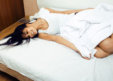 Giovane donna graziosa del tann a letto fra divertiresi bianco degli strati, provando a dormire, imbrogliante intorno Immagine Stock Libera da Diritti