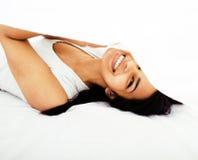 Giovane donna graziosa del tann a letto fra divertiresi bianco degli strati, provando a dormire, imbrogliante intorno, concetto d Fotografie Stock