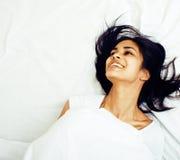 Giovane donna graziosa del tann a letto fra gli strati bianchi divertendosi, TR Fotografie Stock