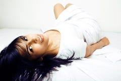 Giovane donna graziosa del tann a letto fra gli strati bianchi divertendosi, TR Immagini Stock