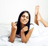 Giovane donna graziosa del tann a letto fra gli strati bianchi divertendosi, TR Immagine Stock