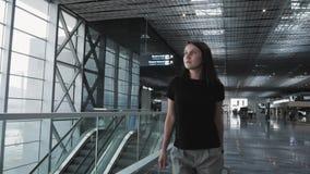 Giovane donna graziosa di affari che cammina all'aeroporto con i suoi bagagli mentre aspettando la sua coda la registrazione, via archivi video