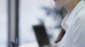 Giovane donna graziosa di affari che parla con il cliente in ufficio, lavorante al computer portatile stock footage