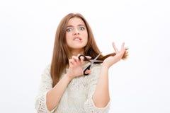Giovane donna graziosa di dubbio incerta che taglia i suoi capelli Fotografia Stock Libera da Diritti