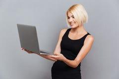 Giovane donna graziosa felice che sorride e che per mezzo del computer portatile Fotografia Stock Libera da Diritti