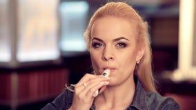Giovane donna graziosa in fumo una sigaretta elettronica al negozio del vape stock footage