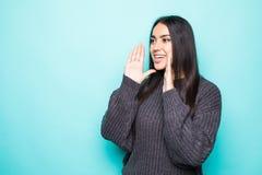 Giovane donna graziosa in maglione caldo che grida sul fondo blu immagini stock libere da diritti