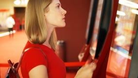 Giovane donna graziosa nel biglietto d'acquisto di film della maglietta rossa dal distributore automatico al cinema archivi video