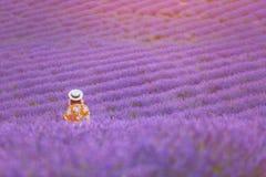 Giovane donna graziosa nel tramonto di sorveglianza d'uso del cappello del vestito arancio lungo in un giacimento della lavanda B immagini stock
