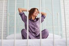 Giovane donna graziosa in pigiami porpora che si siedono sul letto Immagine Stock Libera da Diritti