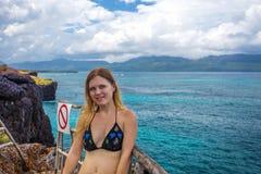 Giovane donna graziosa su fondo del mare dall'alta scogliera Immagini Stock