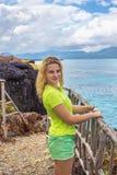 Giovane donna graziosa su fondo del mare dall'alta scogliera Immagine Stock