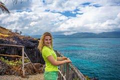 Giovane donna graziosa su fondo del mare dall'alta scogliera Immagine Stock Libera da Diritti