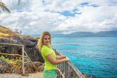 Giovane donna graziosa su fondo del mare dall'alta scogliera Immagini Stock Libere da Diritti
