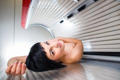 Giovane donna graziosa in un solarium moderno Immagine Stock