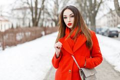 Giovane donna graziosa in una camminata rossa alla moda della sciarpa e del cappotto fotografia stock libera da diritti