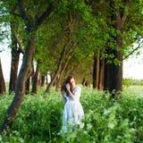 Giovane donna graziosa in vestito bianco lungo e con il ricciolo dorato lungo Fotografia Stock
