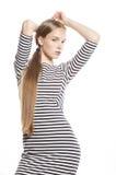 Giovane donna graziosa in vestito elegante dalla striscia isolato Immagini Stock