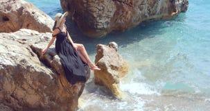 Giovane donna graziosa in vestito elegante nero che si siede sulle rocce vicino al mare archivi video